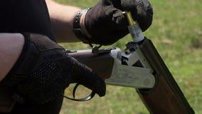 Las manos del ` un s del hombre encargan un rifle de dos cañones de bulet y de los cartuchos almacen de metraje de vídeo