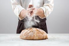 Las manos del varón en harina y barra de pan orgánica rústica Imágenes de archivo libres de regalías