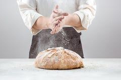 Las manos del varón en harina y barra de pan orgánica rústica Fotografía de archivo libre de regalías