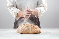 Las manos del varón en harina y barra de pan orgánica rústica Fotos de archivo libres de regalías