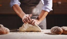 Las manos del varón del ` s del panadero amasan la pasta Fotos de archivo libres de regalías