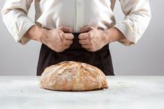 Las manos del varón y la barra de pan orgánica rústica Foto de archivo