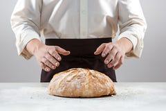 Las manos del varón y la barra de pan orgánica rústica Fotos de archivo libres de regalías