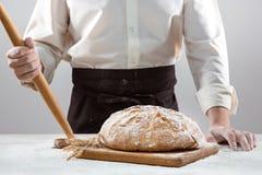Las manos del varón y la barra de pan orgánica rústica Imágenes de archivo libres de regalías