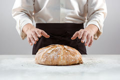 Las manos del varón y la barra de pan orgánica rústica Foto de archivo libre de regalías