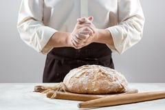 Las manos del varón y la barra de pan orgánica rústica Imagenes de archivo