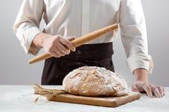 Las manos del varón y la barra de pan orgánica rústica Fotografía de archivo libre de regalías