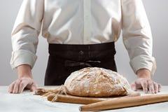 Las manos del varón y la barra de pan orgánica rústica Imagen de archivo