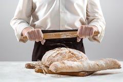 Las manos del varón y la barra de pan orgánica rústica Fotos de archivo