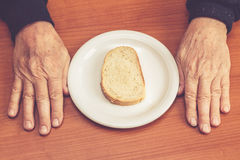 Las manos del viejo hombre en la tabla con una rebanada de pan en centro Foto de archivo