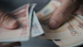 Las manos del viejo hombre que cuentan billetes de banco euro Cierre para arriba almacen de video