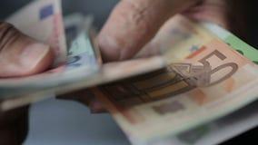 Las manos del viejo hombre que cuentan billetes de banco euro Las manos del hombre cercano del upOld que cuentan billetes de banc metrajes