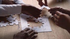 Las manos diversas de hombres de negocios conectan rompecabezas juntas en el escritorio metrajes