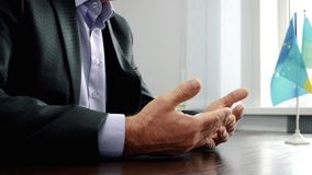 Las manos durante la entrevista, hombre de los hombres en un traje oscuro que se sienta en la tabla metrajes
