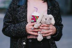 Las manos elegantes jovenes de la muchacha sostienen el café y los juguetes calientes Fotos de archivo