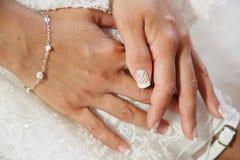 Las manos en el vestido de boda con los clavos blancos manicures imagen de archivo