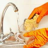 Las manos en guantes con la esponja lavan el vidrio debajo de la agua corriente Imagenes de archivo