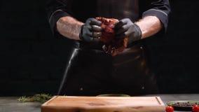 Las manos en guantes de goma negros destrozan el pedazo grande de cierre de la carne para arriba Goteo del jugo en tabla de corta almacen de video