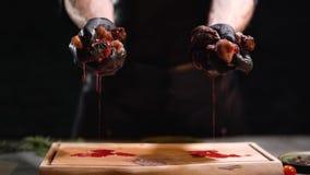 Las manos en guantes de goma negros exprimen dos pedazos de cierre de la carne para arriba Goteo del jugo en tabla de cortar almacen de video