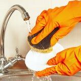 Las manos en los guantes de goma con la esponja lavan la placa debajo de la agua corriente Imagen de archivo libre de regalías