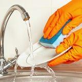 Las manos en los guantes de goma lavan los platos sucios debajo de la agua corriente en cocina Imágenes de archivo libres de regalías