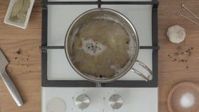 Las manos en potholders sacan la cacerola con el agua hirvienda de la estufa en cocina almacen de video