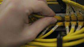 las manos enchufan el cable de Ethernet amarillo metrajes