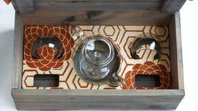 Las manos femeninas abren una caja de regalo de madera con la tetera de cristal y dos tazas almacen de video