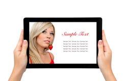 Tableta femenina aislada del asimiento de las manos con una muchacha rubia hermosa a imagen de archivo