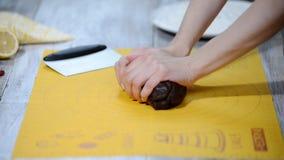 Las manos femeninas amasaron la pasta del chocolate en una tabla blanca para las galletas del Año Nuevo El concepto de clases cul metrajes