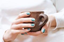 Las manos femeninas con el clavo verde diseñan sostener una taza Foto de archivo