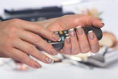 Las manos femeninas con la manicura francesa sostienen el microteléfono Foto de archivo libre de regalías