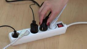 Las manos femeninas conectan los enchufes del alambre con el interruptor de la extensión en piso de madera almacen de metraje de vídeo