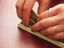 Las manos femeninas consideran dólares Fotografía de archivo libre de regalías