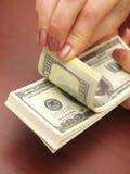 Las manos femeninas consideran dólares Fotografía de archivo