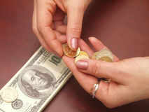 Las manos femeninas consideran monedas Foto de archivo