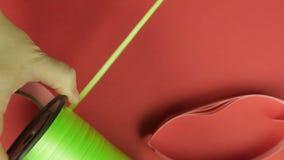 Las manos femeninas cortaron la cinta verde de la bobina con las tijeras Fondo rojo almacen de video