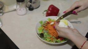 Las manos femeninas cortaron un huevo a una ensalada con paprika y ensalada rojos de la lechuga almacen de metraje de vídeo