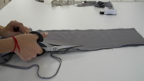 Las manos femeninas cortaron un pedazo de paño gris por una envoltura almacen de video
