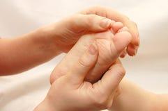 Las manos femeninas dan masajes a un pie de los niños Imagen de archivo libre de regalías