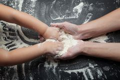Las manos femeninas de la madre enseñan a una niña a cocinar a una hija El concepto de cocinar las galletas hechas en casa, torta imágenes de archivo libres de regalías