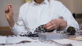 Las manos femeninas del sastre que cosen el pedazo de paño en cosen el estudio almacen de metraje de vídeo