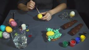 Las manos femeninas depositaron suavemente la pintura blanca en la parte inferior de un huevo coloreado amarillo almacen de metraje de vídeo
