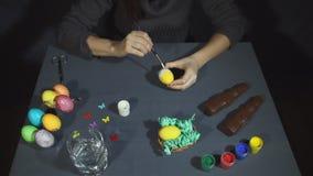 Las manos femeninas depositaron suavemente la pintura blanca en la parte inferior de un huevo coloreado amarillo metrajes