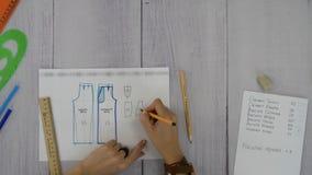 Las manos femeninas dibujan un diagrama
