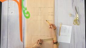Las manos femeninas dibujan una línea recta en el papel con un lápiz y gobiernan metrajes