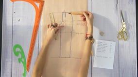 Las manos femeninas dibujan una línea recta en el papel con un lápiz y gobiernan almacen de metraje de vídeo