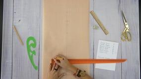 Las manos femeninas dibujan una línea usando una regla, un lápiz y el papel