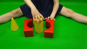 Las manos femeninas doblan una figura de los cubos de diversas formas metrajes