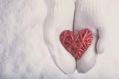 Las manos femeninas en blanco hicieron punto las manoplas con un corazón rojo romántico entrelazado del vintage en una nieve Amor fotos de archivo